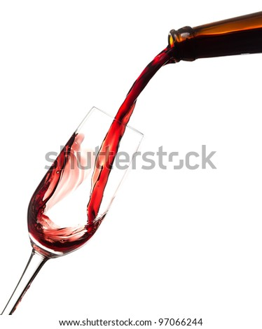 Red wine poured in a glass isolated on white.