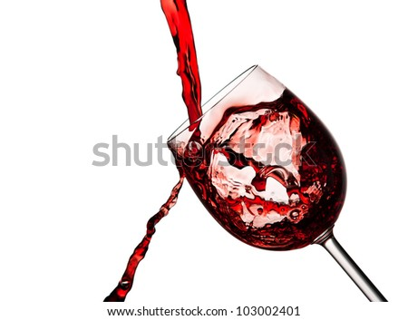 Red wine poured into crystal glass spilling a lot