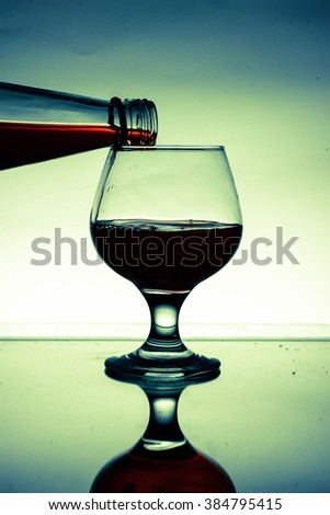 red wine poured into glass in vintage style