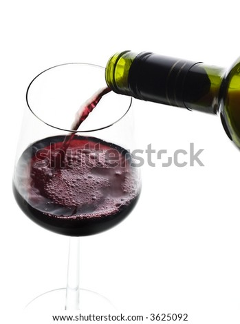 red wine poured to a glass from a bottle - stock photo