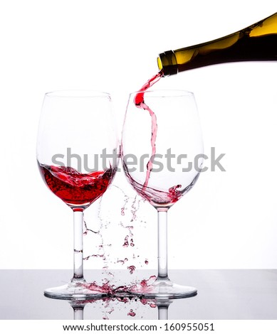 Red wine pouring down from a bottle