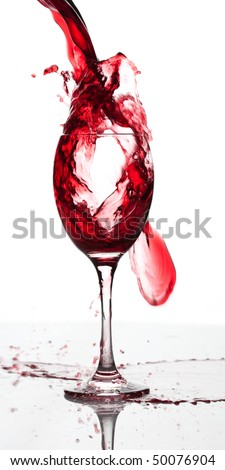 Red wine pouring down into a wine glass isolated on white backgroun
