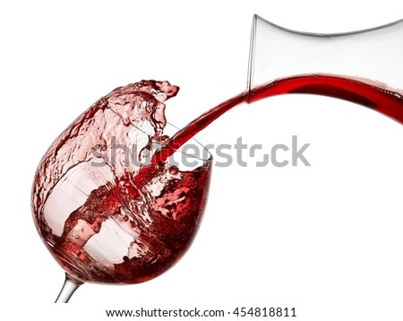 Red wine pouring from a decanter - stock photo