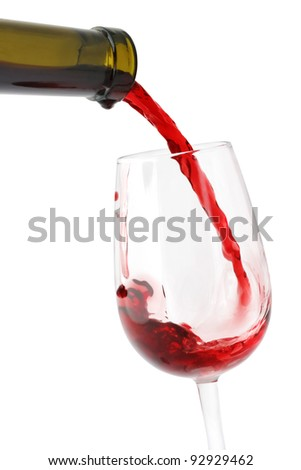 Red wine pouring from the bottle into a wineglass isolated on white background. - stock photo