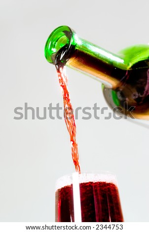 red wine pouring from the bottle into wineglass - stock photo