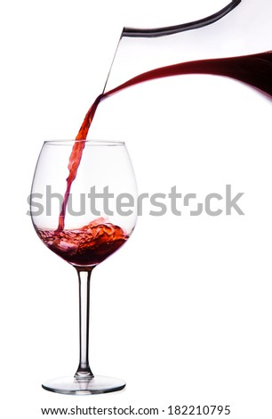 Red wine pouring from the decanter.Isolated on white.