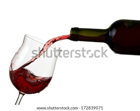 Red wine pouring in a glass from a bottle - stock photo