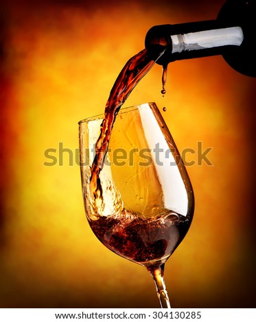 Red wine pouring in a wineglass on orange background
