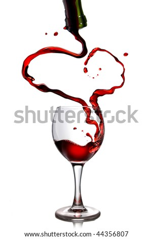 Red wine pouring in goblet from bottle in shape of heart - stock photo
