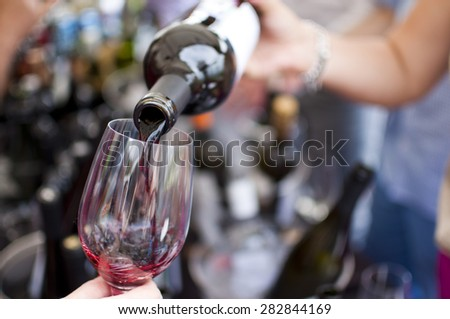 Red wine pouring in the glass at wine market - stock photo