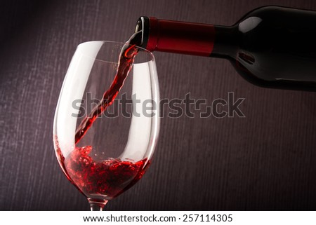 Red wine pouring into a glass - stock photo