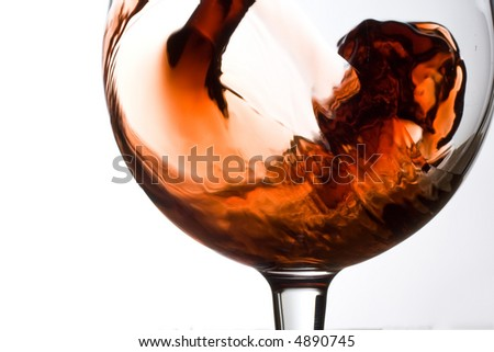 Red wine pouring into a glass isolated on white background