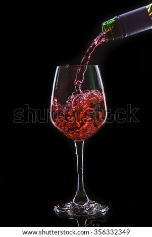 Red wine pouring into a wine glass. Isolated on black background - stock photo