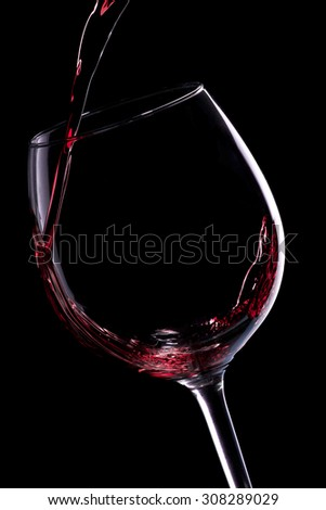 Red wine pouring into a wine glass  on black background - stock photo