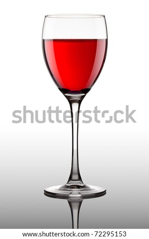 red wine pouring into glass on gray background - stock photo
