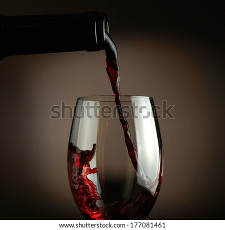 Red wine pouring into glass over dark background - stock photo