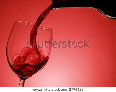Red wine pouring into the glass over red background - stock photo