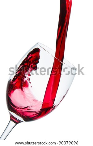 red wine pouring into wine glass isolated - stock photo