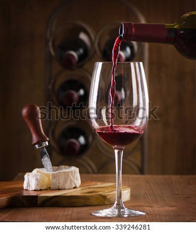 Red wine pouring into wine glass.  Selective focus  - stock photo