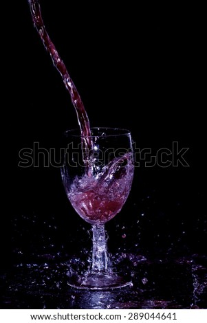 red wine pouring on black background