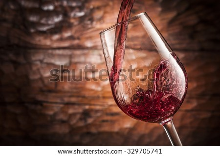red wine pouring on wood background