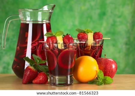 Red wine punch called sangria mixed orange, apple and mango, garnished with strawberries and pineapple with a jug of sangria and fruits (Selective Focus, Focus on the fruits on the skewer in front) - stock photo