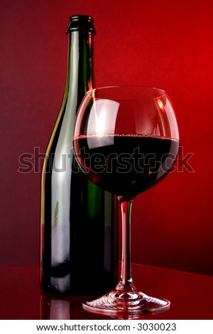 Red wine. Red wine glass and green wine bottle.Placed on glass surface, small mirror reflection.Red light background light.Wine bubbles chain in the glass.