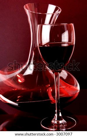 Red wine. Red wine wine glass and wine jug detail.Placed on glass  surface, small mirror reflection.Red color background light.