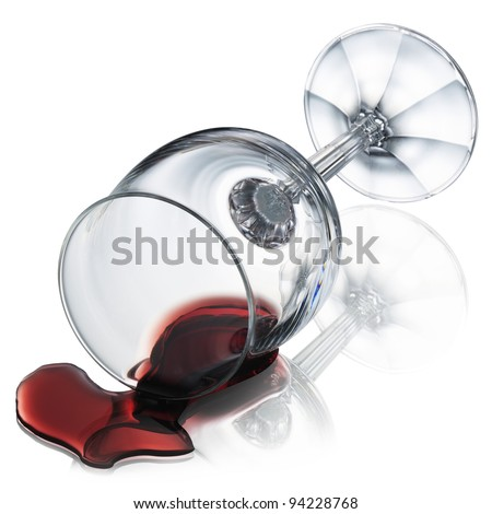 Red wine spilled from wineglass on glass table - stock photo