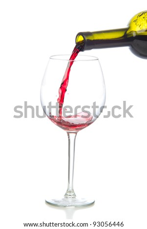 Red wine splash being poured into a wine glass isolated on a white background - stock photo