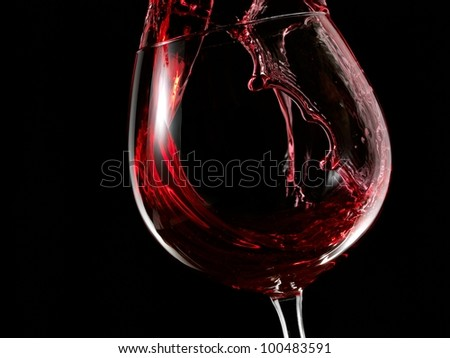 Red wine splash in a glass - stock photo