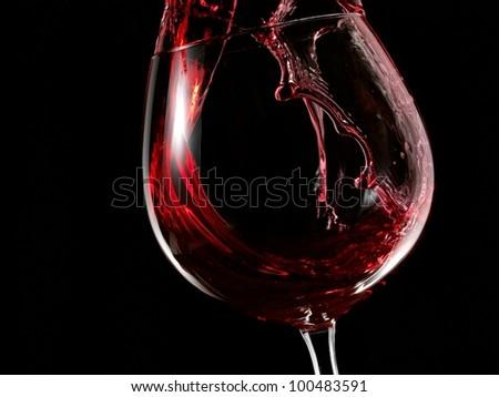 Red wine splash in a glass - stock photo