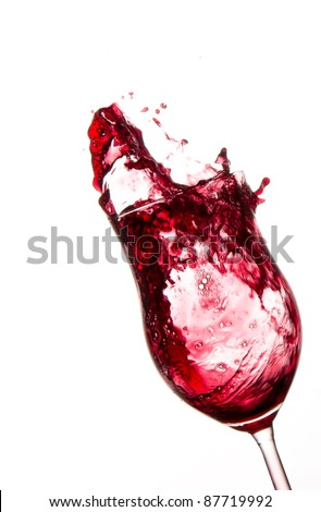Red wine splashing out of glass, isolated on white background