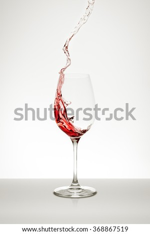 red wine splashing out of the glass - stock photo