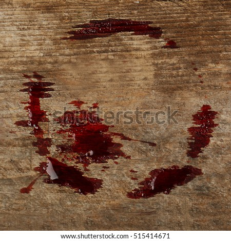 Red wine stain on wooden background