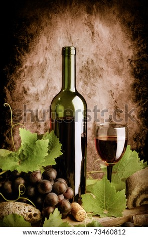 Red wine still life in old style with grunge wall background - stock photo