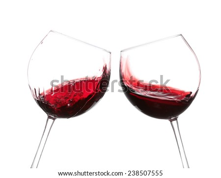 red wine swirling in a goblet wine glass, isolated on a white background - stock photo