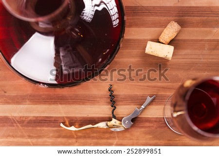 Red wine. Top view of decanter and wineglass with red wine on the wooden table  - stock photo