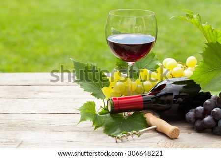 Red wine, wine bottle and grape on wooden table with copy space