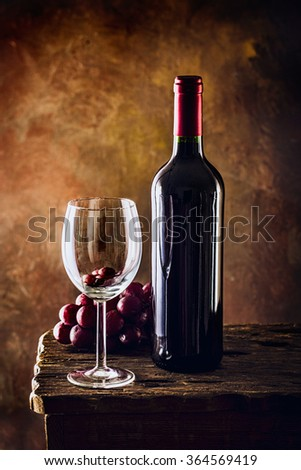 Red wine. Wine bottles in vintage cellar. Red grapes with wine - stock photo