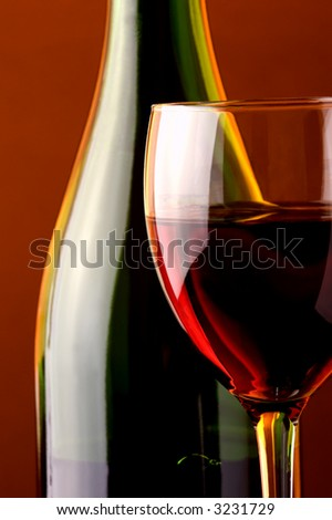 Red wine. Wine glass and green wine bottle-details.Warm background light.