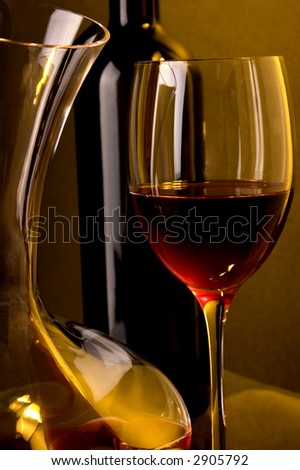 Red wine , wine jug detail and wine glass detail. Black wine bottle at back. Low yellow background light.