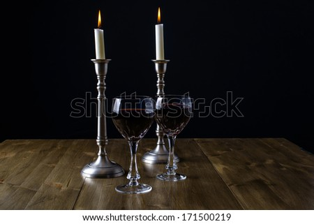 Red Wine with candles on wood table - stock photo