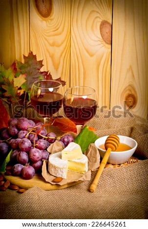 Red wine with cheese, honey, almonds and grapes on sackcloth on a background of a wooden wall and autumn leaves - stock photo