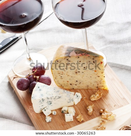 red wine with cheese on chopping board - stock photo