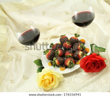 Red wine with chocolate covered strawberries, chocolate covered apricots and rose - stock photo