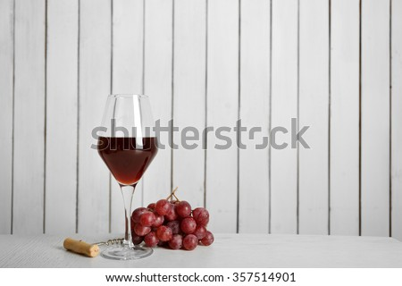 Red wine with grape on wooden wall background - stock photo