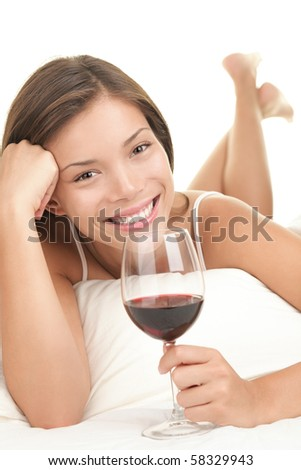 Red wine. Woman drinking red wine in bed. Asian-Caucasian female model. White background. - stock photo