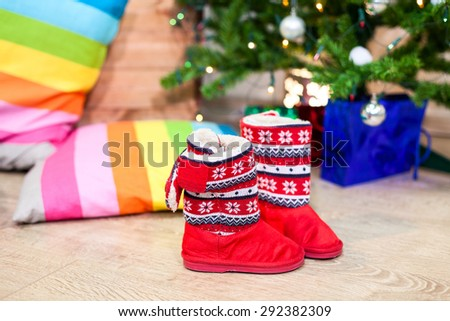 Red winter boots next to decorated Christmas tree with toys and gifts - stock photo