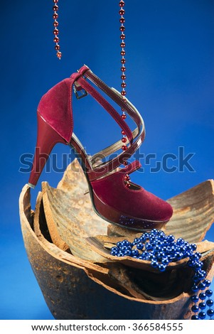Red woman high heels with pearls on broken retro jug over blue backgrounds - stock photo